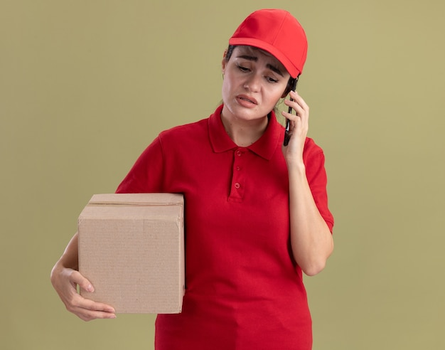 Stirnrunzelnde junge lieferfrau in uniform und mütze mit karton, die am telefon spricht, isoliert auf olivgrüner wand mit kopierraum