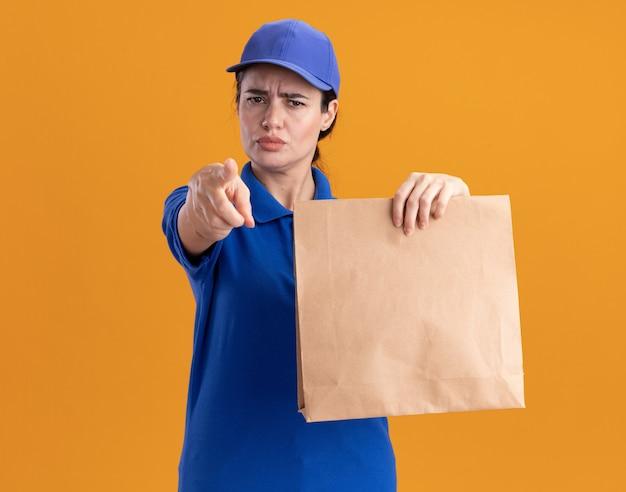 Stirnrunzelnde junge lieferfrau in uniform und mütze mit papierpaket, die auf die kamera schaut und zeigt