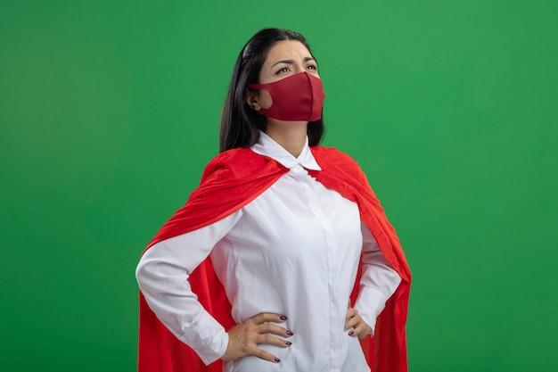 Stirnrunzelnde junge superfrau mit maske, die hände auf ihren hüften hält, die lokal auf grüner wand suchen