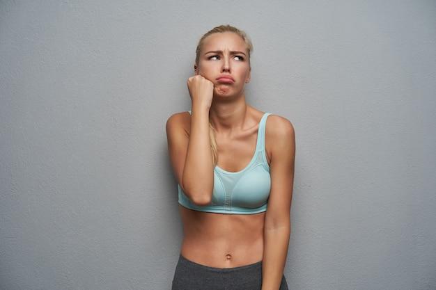 Stirnrunzelnde traurige junge schlanke blonde frau, die beiseite schaut und ihre lippen schmollt, kopf auf erhobene hand lehnt, während sie über grauem hintergrund steht, gekleidet in sportliche abnutzung