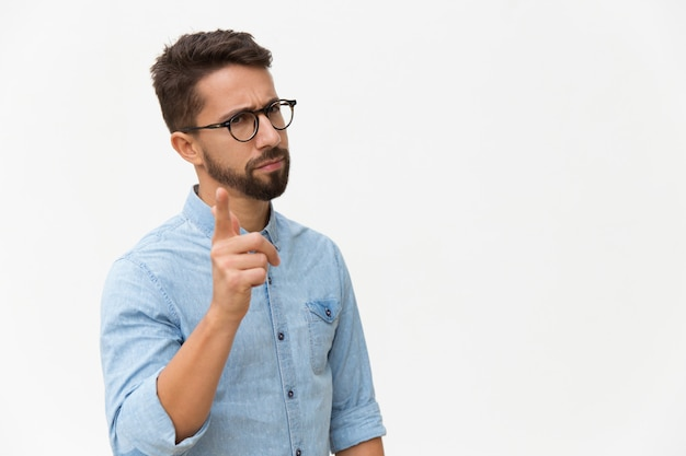 Stirnrunzelnder betroffener kerl, der finger rüttelt