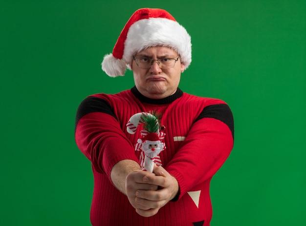 Stirnrunzelnder erwachsener mann, der brille und weihnachtsmütze trägt, streckt zuckerstangenverzierung in richtung kamera aus, die kamera lokalisiert auf grünem hintergrund betrachtet