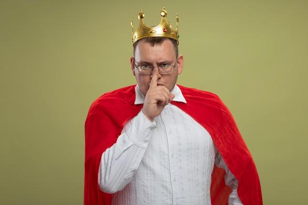 Stirnrunzelnder erwachsener slawischer superheldenmann im roten umhang, der brille und krone trägt, die stille geste tun, die auf olivgrüner wand mit kopienraum lokalisiert wird