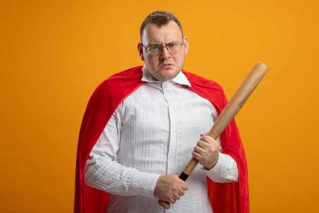 Stirnrunzelnder erwachsener slawischer superheldenmann im roten umhang, der brillen hält, die baseballschläger lokalisiert auf orange wand mit kopienraum halten