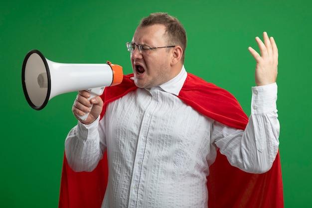 Stirnrunzelnder erwachsener slawischer superheldenmann im roten umhang, der brillen trägt, die im lautsprecher schreien, der hand in der luft hält, die seite betrachtet, die auf grüner wand lokalisiert wird