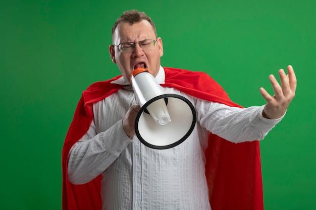 Stirnrunzelnder erwachsener slawischer superheldenmann im roten umhang, der brillen trägt, streckt hand aus, die seite betrachtet, die durch sprecher spricht, der auf grüner wand lokalisiert wird