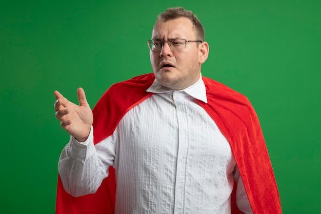 Stirnrunzelnder erwachsener superheldenmann im roten umhang, der brillen trägt, die seite betrachten, die hand lokalisiert auf grüner wand streckt