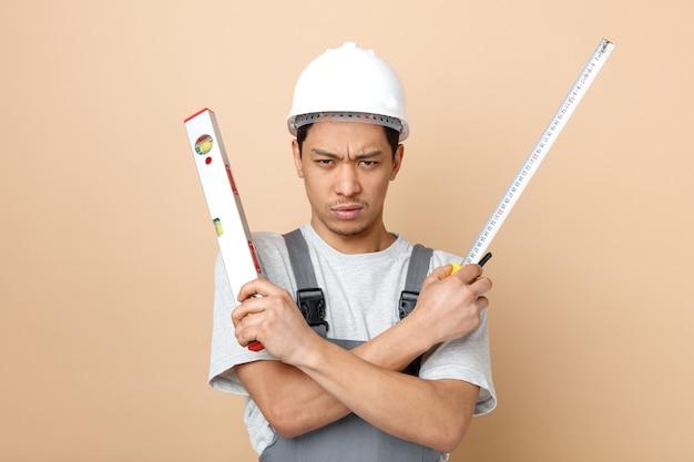 Stirnrunzelnder junger bauarbeiter, der schutzhelm und uniform hält, die hände gekreuzt halten, die gerade lineal und bandmesser halten