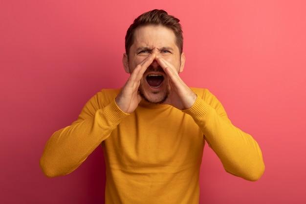 Stirnrunzelnder junger blonder gutaussehender mann, der die hände in der nähe des mundes hält und laut nach jemandem ruft, der isoliert auf einer rosa wand ist?