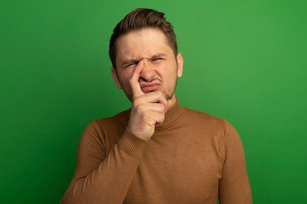 Stirnrunzelnder junger blonder gutaussehender mann, der finger auf die nase legt und isoliert auf grüner wand schaut
