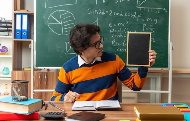Stirnrunzelnder junger geometrielehrer mit brille, der am schreibtisch mit schulmaterial im klassenzimmer sitzt und eine mini-tafel zeigt, die darauf schaut?