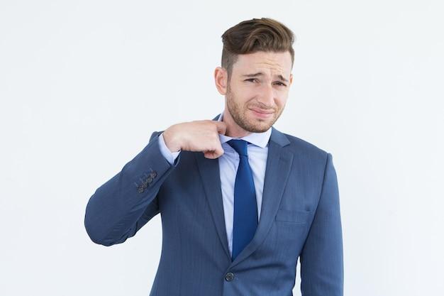 Stirnrunzelnder junger geschäftsmann, der die krawatte abbricht