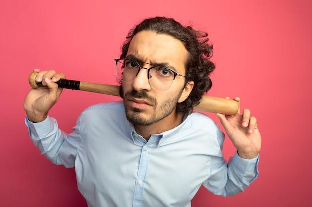 Stirnrunzelnder junger gutaussehender mann, der eine brille hält, die baseballschläger hinter dem nacken hält, der vorne auf rosa wand lokalisiert betrachtet