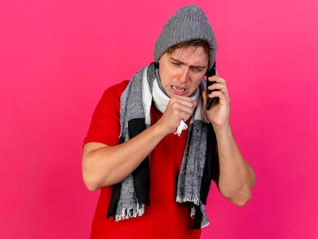 Stirnrunzelnder junger hübscher blonder kranker mann, der wintermütze und schal trägt, die am telefon sprechen serviette halten hand in der nähe des mundes hustet und nach unten isoliert auf rosa wand mit kopienraum schaut