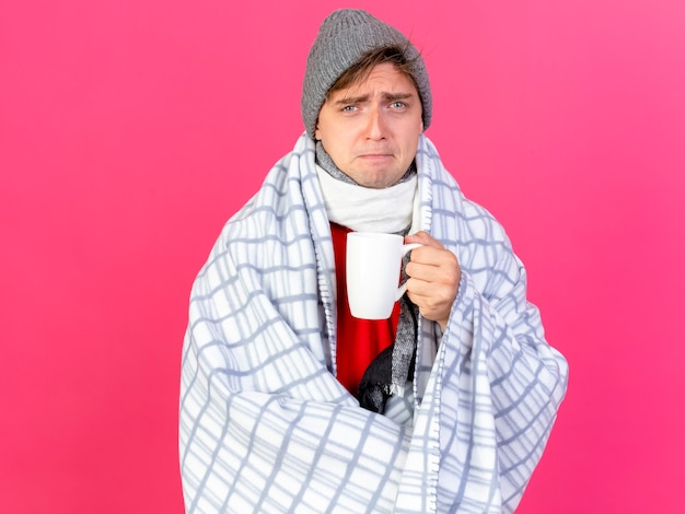 Stirnrunzelnder junger hübscher blonder kranker mann, der wintermütze und schal trägt, die im plaid eingewickelt halten tasse des tees lokalisiert auf rosa wand