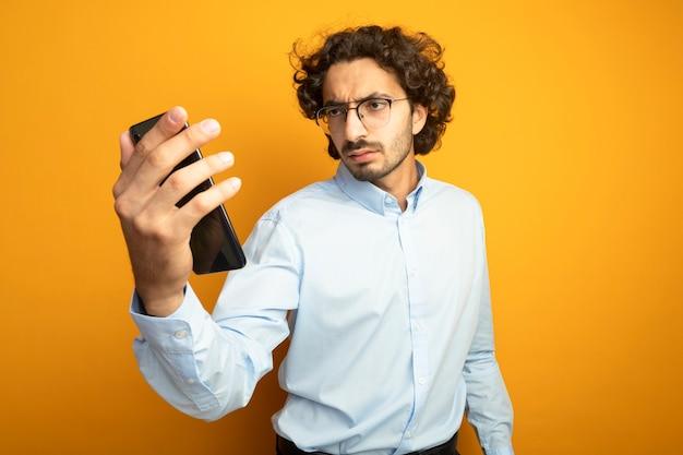 Stirnrunzelnder junger hübscher kaukasischer mann, der brillen hält und handy lokalisiert auf orange hintergrund mit kopienraum hält