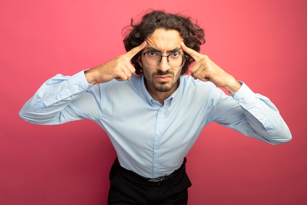 Stirnrunzelnder junger hübscher kaukasischer mann, der eine brille trägt, die denkgeste lokalisiert auf purpurroter wand tut