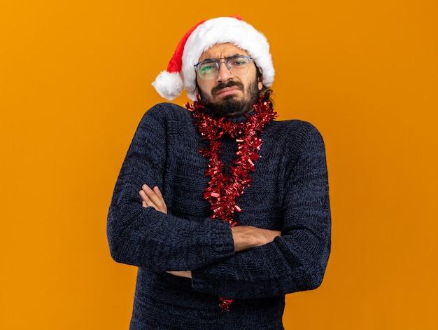 Stirnrunzelnder junger hübscher kerl, der weihnachtshut mit girlande am hals kreuzt hände lokalisiert auf orange hintergrund trägt