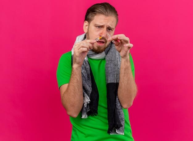 Stirnrunzelnder junger hübscher kranker mann, der schal hält spritze und ampulle betrachtet sie lokalisiert auf rosa wand