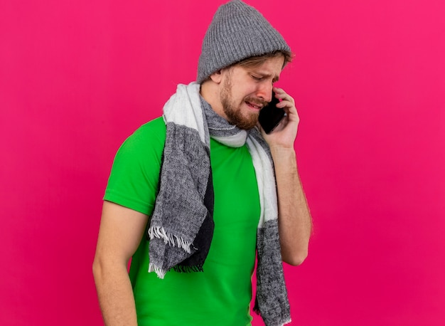Stirnrunzelnder junger hübscher kranker mann, der wintermütze und schal trägt, die am telefon mit geschlossenen augen sprechen, die auf rosa wand lokalisiert werden