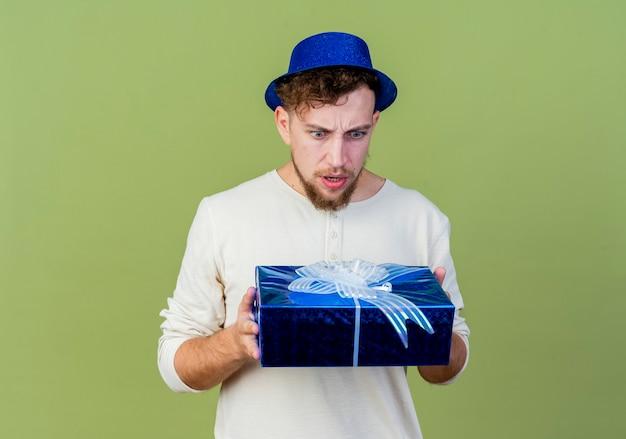 Stirnrunzelnder junger hübscher party-typ, der partyhut hält und geschenkbox isoliert auf olivgrüner wand hält
