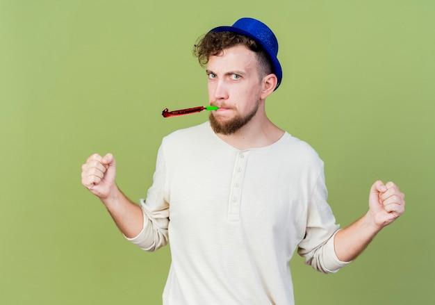 Stirnrunzelnder junger hübscher party-typ, der partyhut trägt, der frontblasen-partygebläse mit geballten fäusten betrachtet, die auf olivgrüner wand isoliert werden