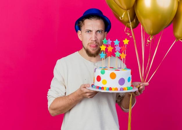 Stirnrunzelnder junger hübscher slawischer party-typ, der partyhut hält, der luftballons und geburtstagstorte mit sternen hält, die front betrachten, die zunge lokalisiert auf rosa wand mit kopienraum zeigt