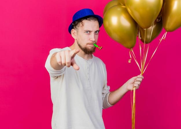 Stirnrunzelnder junger hübscher slawischer party-typ, der partyhut hält, der luftballons und partygebläse hält und nach vorne zeigt, lokalisiert auf rosa wand mit kopienraum