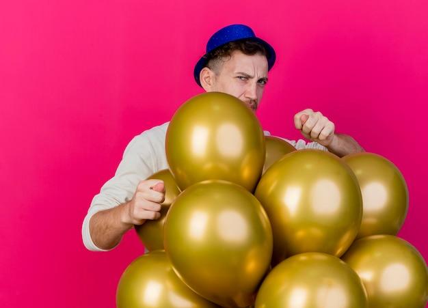 Stirnrunzelnder junger hübscher slawischer party-typ, der partyhut trägt, der hinter luftballons steht, die front betrachten feigenzeichen lokalisiert auf rosa wand