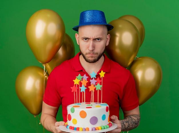 Stirnrunzelnder junger hübscher slawischer party-typ, der partyhut trägt, der vor ballons hält, die geburtstagstorte halten, die kamera lokalisiert auf grünem hintergrund betrachtet