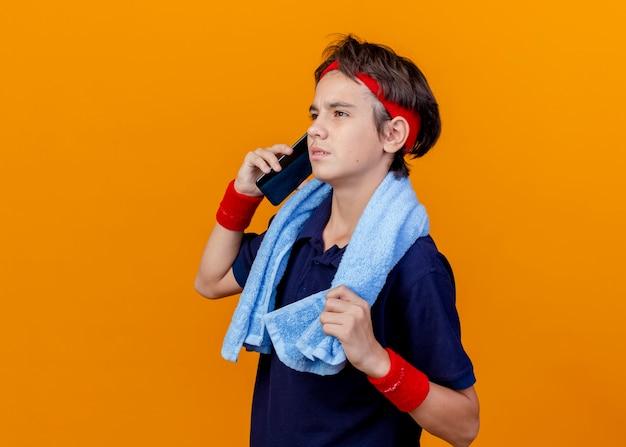 Stirnrunzelnder junger hübscher sportlicher junge, der am telefon spricht