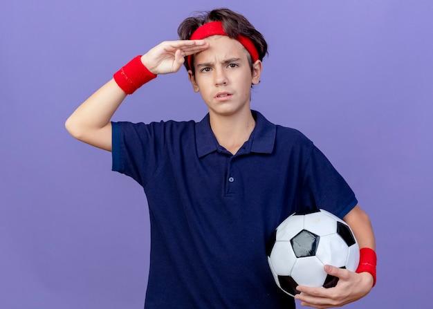Stirnrunzelnder junger hübscher sportlicher junge, der stirnband und armbänder mit zahnspangen hält, die fußball betrachten, der front betrachtet, die hand auf stirn lokalisiert auf lila wand hält