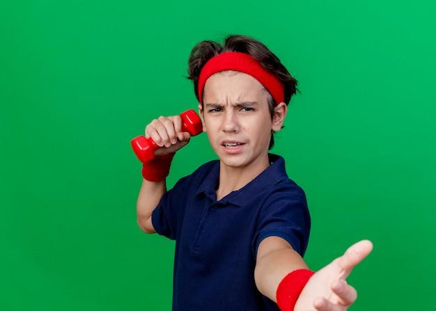 Stirnrunzelnder junger hübscher sportlicher junge, der stirnband und armbänder mit zahnspangen hält, die hantel halten, die hand in richtung lokalisiert auf grüner wand mit kopienraum ausdehnt