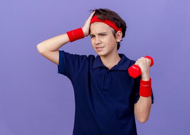 Stirnrunzelnder junger hübscher sportlicher junge, der stirnband und armbänder mit zahnspangen hält, die hantel halten hand auf kopf halten, die seite lokalisiert auf lila wand betrachtet