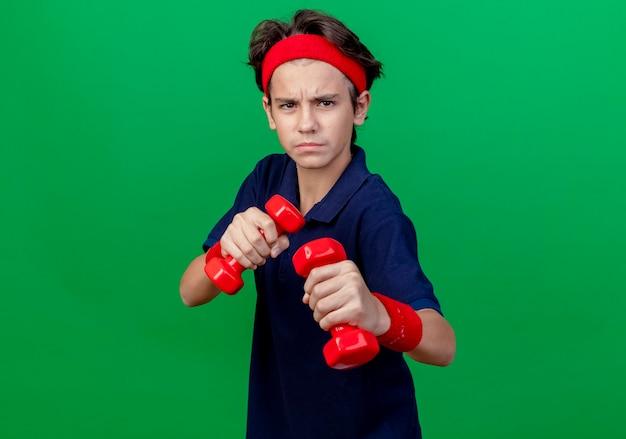 Stirnrunzelnder junger hübscher sportlicher junge, der stirnband und armbänder mit zahnspangen hält, die hanteln halten, die boxgeste tun, lokalisiert auf grüner wand mit kopienraum