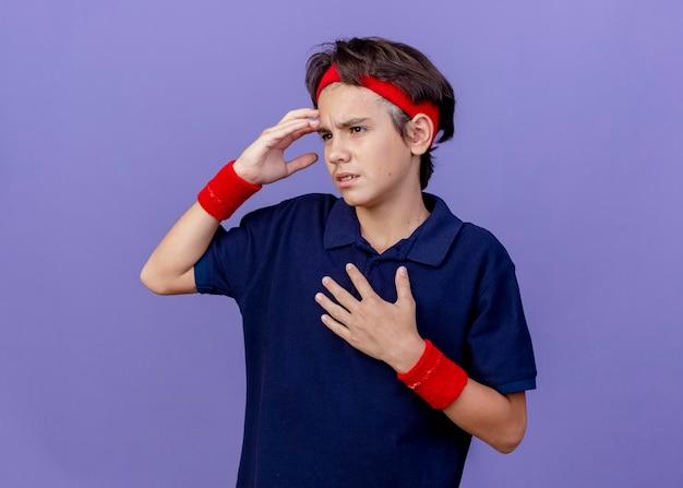 Stirnrunzelnder junger hübscher sportlicher junge, der stirnband und armbänder mit zahnspangen trägt, die seite betrachten, die hand auf brust hält berührenden kopf lokalisiert auf lila wand mit kopienraum