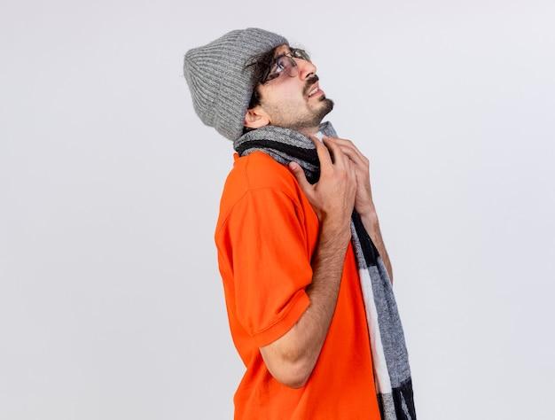Stirnrunzelnder junger kaukasischer kranker mann, der brillenwintermütze und -schal steht, die in der profilansicht stehen und hände auf schal schauen, der lokalisiert auf weißem hintergrund mit kopienraum schaut