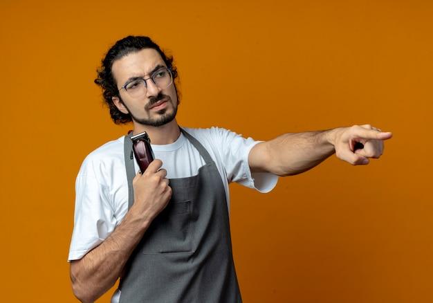 Stirnrunzelnder junger kaukasischer männlicher friseur mit brille und welligem haarband in uniform, der haarschneidemaschinen hält und gerade zeigt