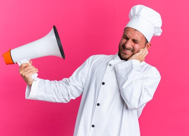 Stirnrunzelnder junger kaukasischer männlicher koch in kochuniform und mütze, der die hand auf dem gesicht hält und den lautsprecher mit geschlossenen augen isoliert auf rosa wand hält