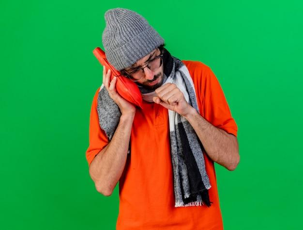 Stirnrunzelnder junger kranker mann, der brille wintermütze und schal trägt, die heißen wasserbeutel auf gesicht hustend halten, faust nahe mund lokalisiert auf grüner wand halten