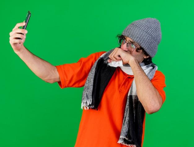 Stirnrunzelnder junger kranker mann, der brillenwintermütze und -schal nimmt selfie hält serviette hält hand auf mund lokalisiert auf grüner wand