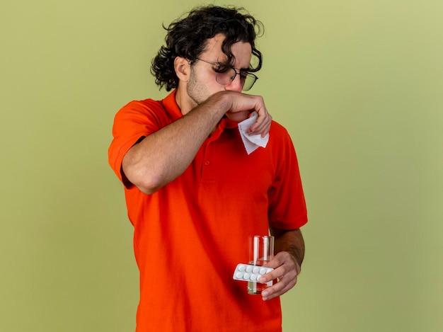 Stirnrunzelnder junger kranker mann, der eine brille hält, die packung der tabletten und des glases des wassers mit der serviette hält, die mund mit geschlossenen augen berührt, lokalisiert auf olivgrüner wand mit kopienraum