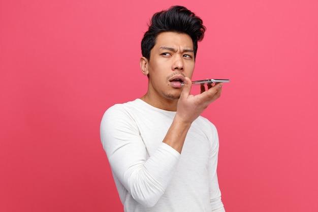 Stirnrunzelnder junger mann, der handy nahe mund hält, der durch sein mikrofon spricht, das zur seite schaut