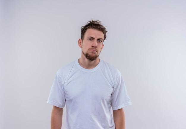 Stirnrunzelnder junger mann, der weißes t-shirt auf isolierter weißer wand trägt
