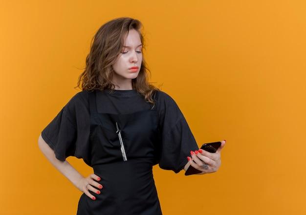 Stirnrunzelnder junger slawischer weiblicher friseur, der uniform hält und handy betrachtet, das hand auf taille hält, lokalisiert auf orange hintergrund mit kopienraum