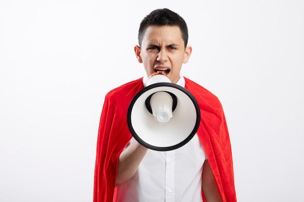 Stirnrunzelnder junger superheldenjunge im roten umhang, der kamera betrachtet, die durch sprecher lokalisiert auf weißem hintergrund mit kopienraum spricht