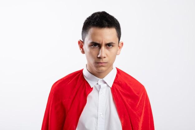 Stirnrunzelnder junger superheldenjunge im roten umhang, der kamera lokalisiert auf weißem hintergrund betrachtet