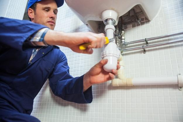 Stirnrunzelnder klempner, der waschbecken repariert