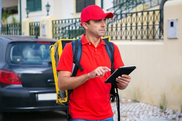 Stirnrunzelnder kurier stehend und adresse über tablette in händen beobachtend. nachdenklicher lieferbote, der bestellung im thermorucksack liefert und rotes hemd und kappe trägt. lieferservice und online-shopping-konzept