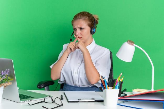 Stirnrunzelndes junges blondes callcenter-mädchen mit headset am schreibtisch sitzend mit arbeitswerkzeugen, das auf den laptop schaut und keine geste macht